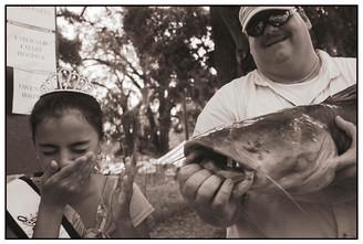 Little Miss Blountstown having to kiss the winning catfish