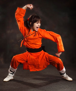 girl in an orange suit performs the form