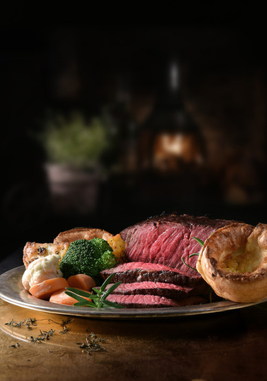 Succulent side of rare roast beef with seasonal vegetables, Yorkshire Puddings and roast p