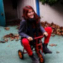 Morgane Grébert alias Melle Rouge sur un tricycle rouge de son ancienne école