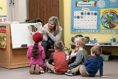 teacher reading to children and showing them the pictures