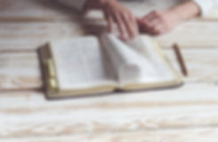 person turning a page in the Bible