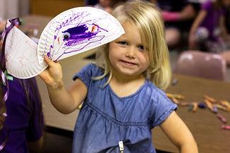 little girl holding her artwork and smiling