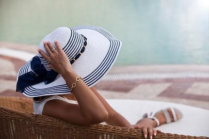 Woman in straw hat relaxing near swimmin