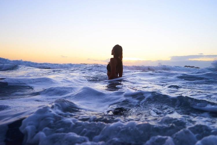 Woman Silhouetted Against Sunrise Or Sunset Rises Half-Way Out Of Blue Ocean Waves When Toxic People Attack Relationship Break-Up Self Improvement Lifestyle Advice Blog Fabsolutely Co