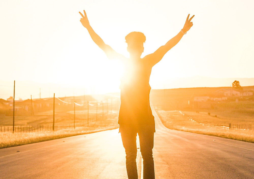 Golden Yellow Silhouette Of Person Raising Both Arms Up and Out With Fingers In V- Peace Signs In The Middle Of A Golden Road Between Two Golden Fields