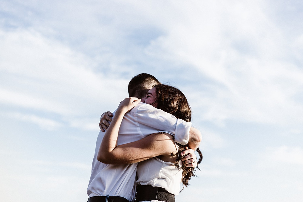 A Enraptured Brown-Haired Couple In White Shirts Joyously Hug Each Other Tightly Under A Blue Sky Full Of Cirrus Clouds
