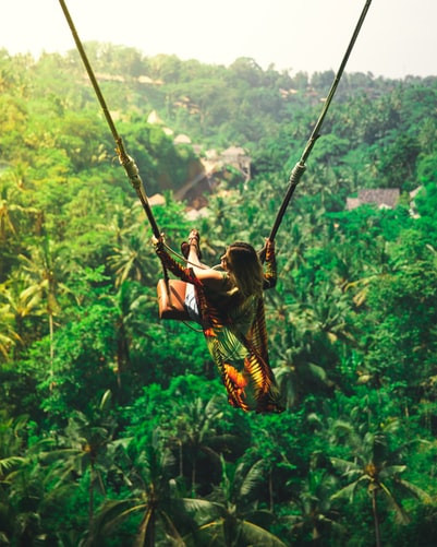 Person In Flowing Orange Garb Swings On Wooden Swing Over Lush Rolling Jungle Hills, Looking Free And Happy
