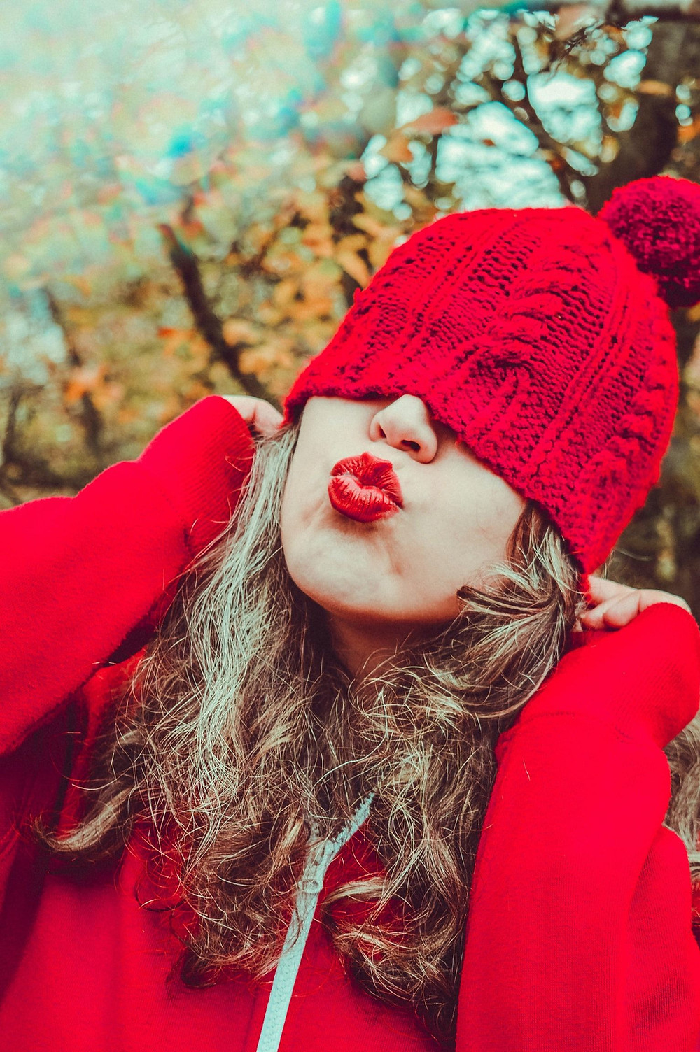 A Close-Up Of A Person With Light Brown Loosely Curly Hair In A Bright Red Hoodie Jacket And Matching Bright Red Yarn Knitted Hat Pulled Over Their Eyes, Puckers Up Their Bright Red Lipsticked Lips As If About To Kiss