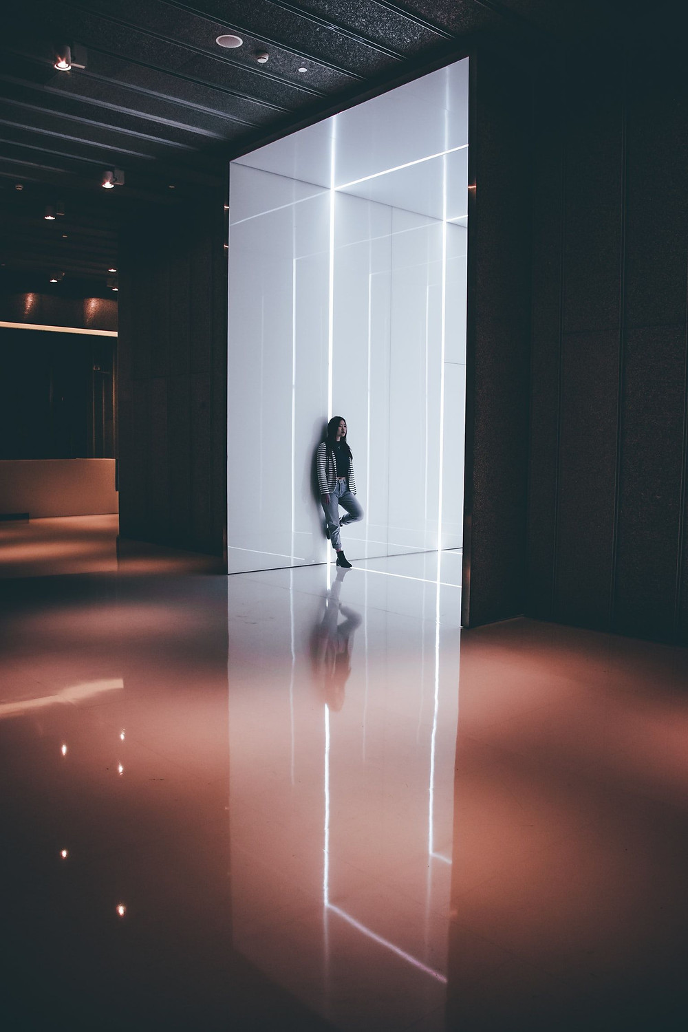 In A Large, Very Dimly Lit, Gallery-Exhibit Like Chamber, A White Wall With A Grid Of Lights Is Leaned Against By An Asian In Gray Jeans, Gray Cardigan, Black Boots, And Black Shirt, With A Solemn And Distant Look On Their Face