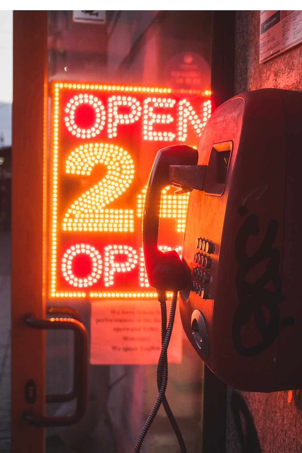 "Behind The Dark Silhouette Of A Grafittied-On Public Telephone, A Rectangular Orange Neon-Glo L.E.D. Lighted Sign Glows: ""Open 24 Open"""