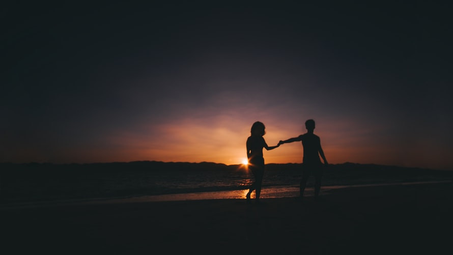 Black Except For The Center Of The Image Where A Sun Sets Orange and Dark Blue Behind A Low Island Ridge With Ocean In Front; A Couple Reaches Out And Holds Hands Silhouetted On The Beach How Do I Break Up With Someone I Just Can't Quit Relationship Break-Up Self Improvement Lifestyle Advice Blog Fabsolutely Co
