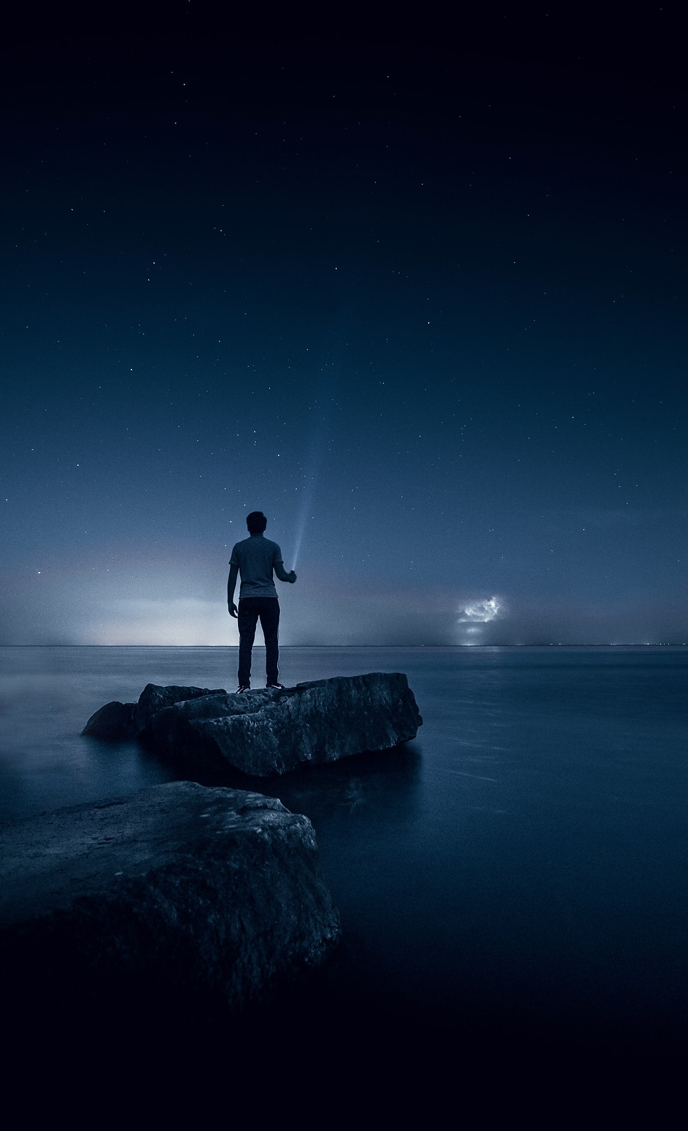 Person Stands On Rock Sticking Out Of Water, Pointing A Beam Of Light Towards A Bright Starry Sky Everything Has A Blue Cast How Can I Make My Life Exciting Relationship Break-Up Self Improvement Lifestyle Advice Blog Fabsolutely Co