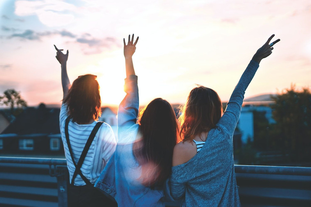 Three People Face A Beautiful Sunrise And Raise Their Arms Towards It In Joy