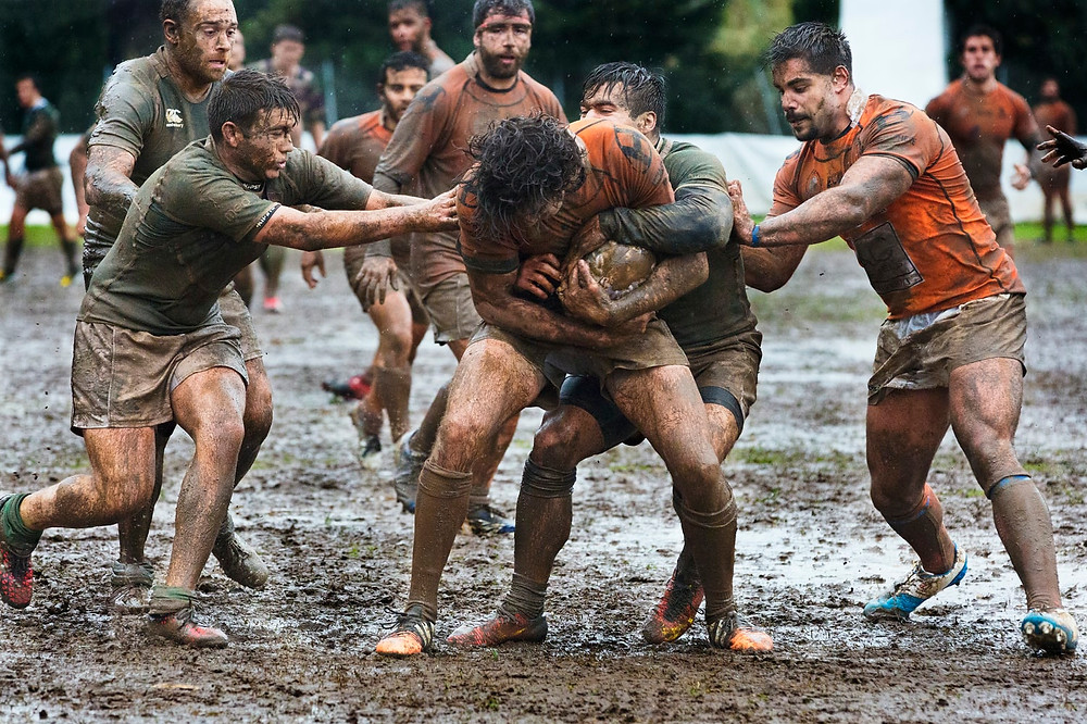 Football Soccer Players Dressed In Shorts And T-Shirts COATED In Mud All Approach The Man With The Ball To Try To Wrestle It Away From Him While He Tries To Curl Around It, A Pictorial Metaphor For Relationship Game-Playing, Fighting, Explaining, Power Plays, Transactional Analysis