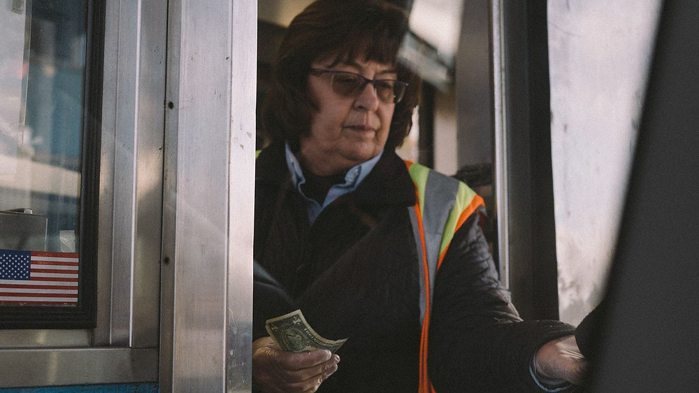 An American Tollbooth Worker In A Reflective Vest, Reaches Out And Takes American Dollars From Unseen Victims