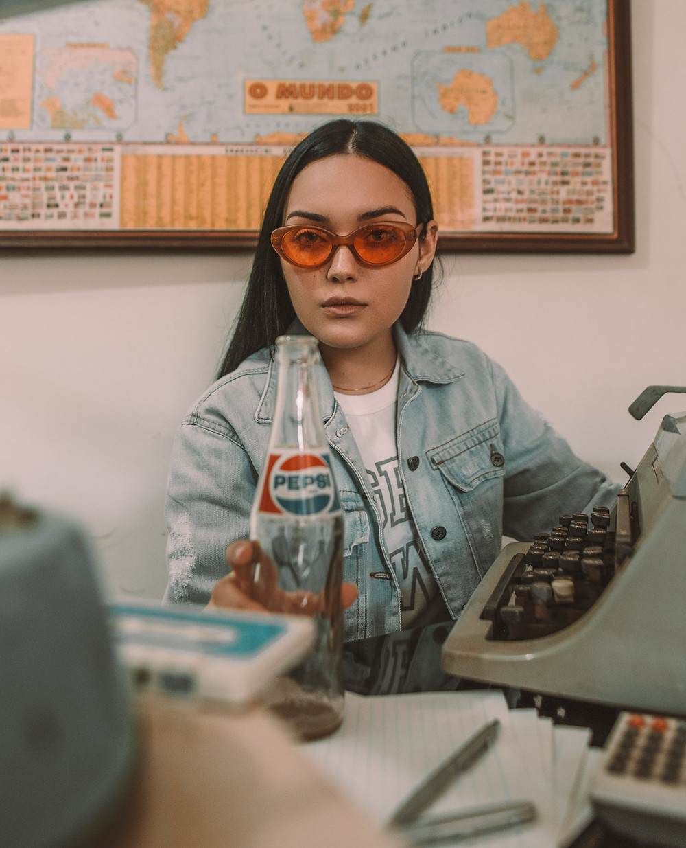 Latina Girl In A Blue Denim Jacket And White Shirt Sits In Front Of A World Map With A Empty VIntage Pepsi Glass Bottle And Grey-Green Typewriter Write Your Own Lifestyle Permission Slip Relationship Break-Up Self Improvement Lifestyle Advice Blog Fabsolutely Co