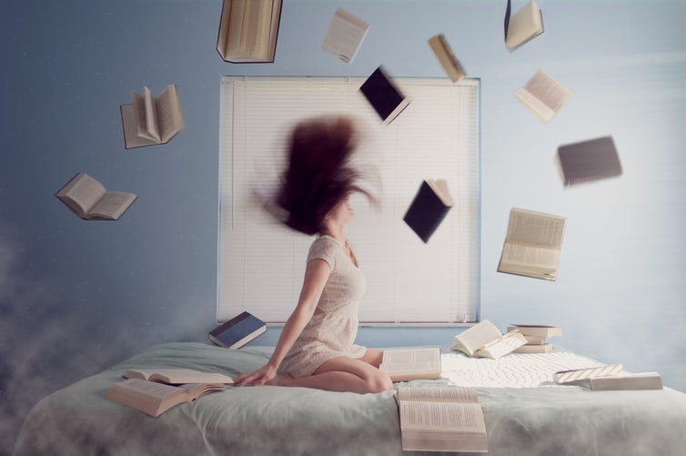 Person With Hair Sweeping Above Them In Motion In Blue Bedroom On White-Covered Bed Surrounded By Books Both On The Bed And Sweeping Across The Air Above Dictionary Of Relationship Portmanteaus Relationship Break-Up Self Improvement Lifestyle Advice Blog Fabsolutely Co