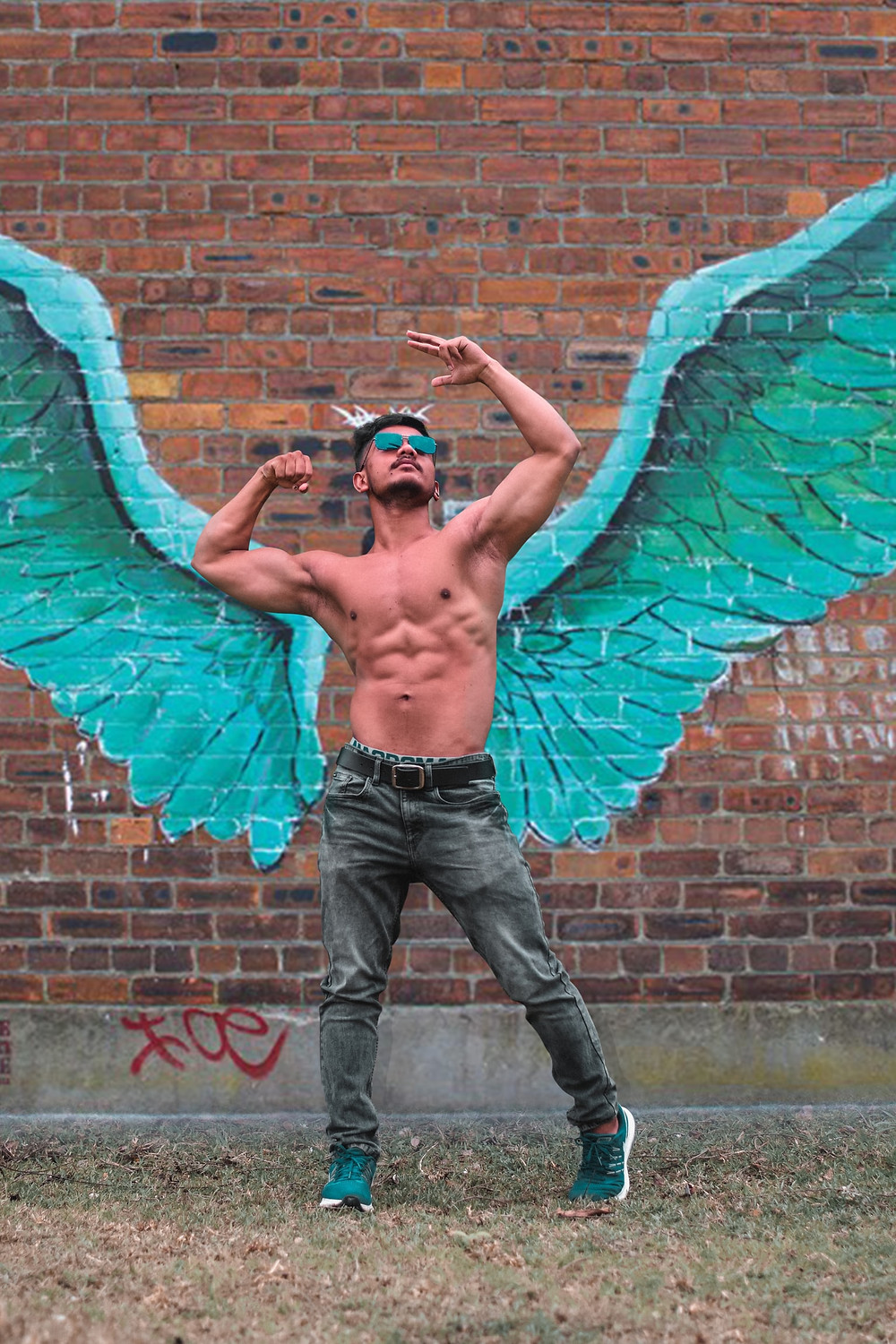 Muscular Topless Hispanic Man In Jeans, Sunglasses, And Teal Tennis Shoes Poses Heroically With Arms Raised In The Air In Front Of A Brick Wall With Huge Teal Angel Wings Painted In Mural Behind Him In A Relationship With A Pick-Up Artist Relationship Break-Up Self Improvement Lifestyle Advice Blog Fabsolutely Co
