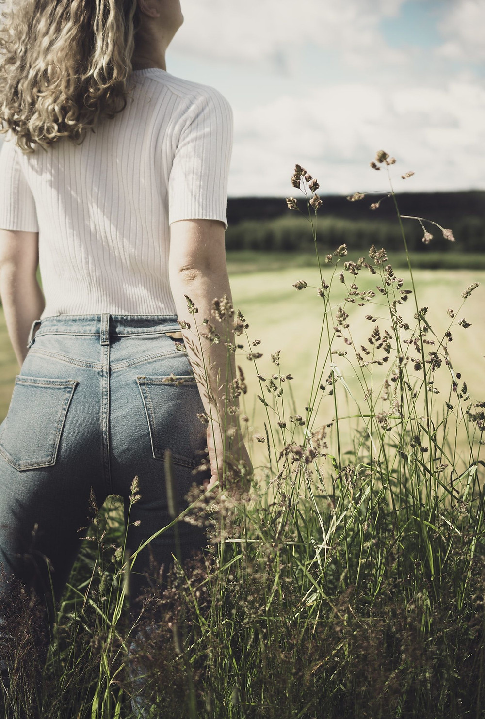 Person In White, Vertically Ribbed Sweater-Shirt And Pale Blue Jeans Faces Away From The Camera, Wavy Brown Blond Hair Touches Squared Shoulders In A Determined Stance As If Refusing Something Behind Them, Amidst Tall, Seed-Topped Grasslands