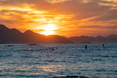 Swimmers, SUP paddlers and Hawaiian canoes at sunrise