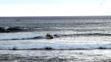 Boys surf in an open canoe