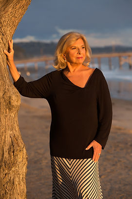 Zaida Buarque, sueter preto, sol de tarde na praia
