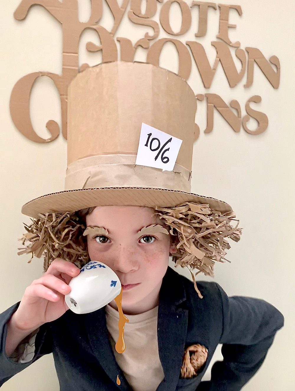 Mad Hatter drinking from a cup of tea, in a cardboard costume made from up cycled material