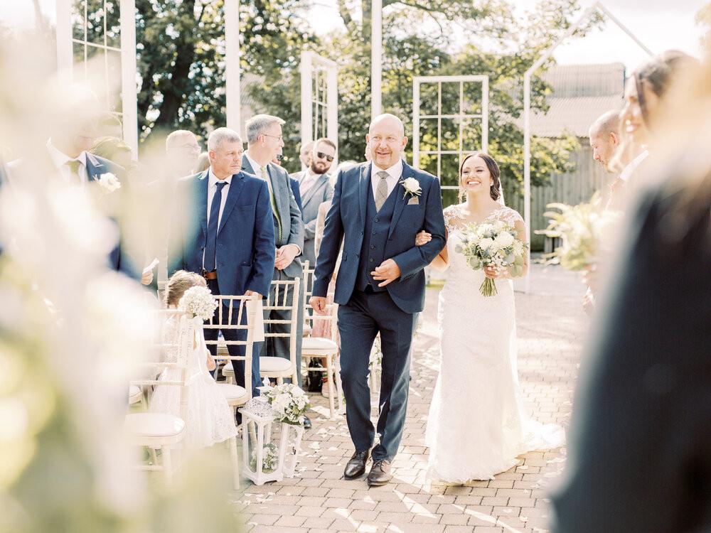 Walking down the outdoor aisle at Alcumlow Wedding Barn
