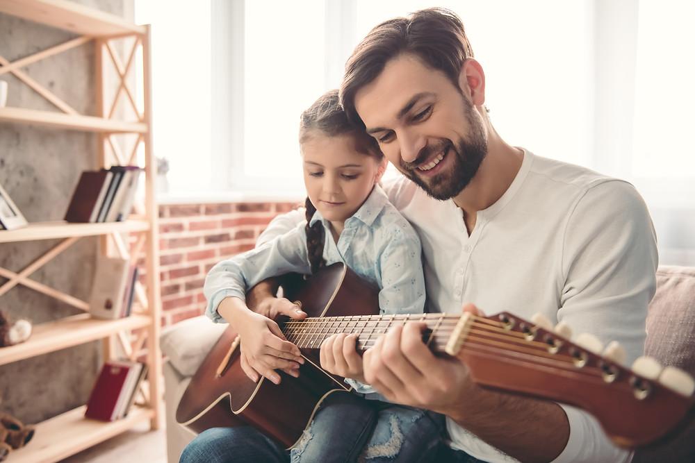 Pai ensinando a filha tocar violão