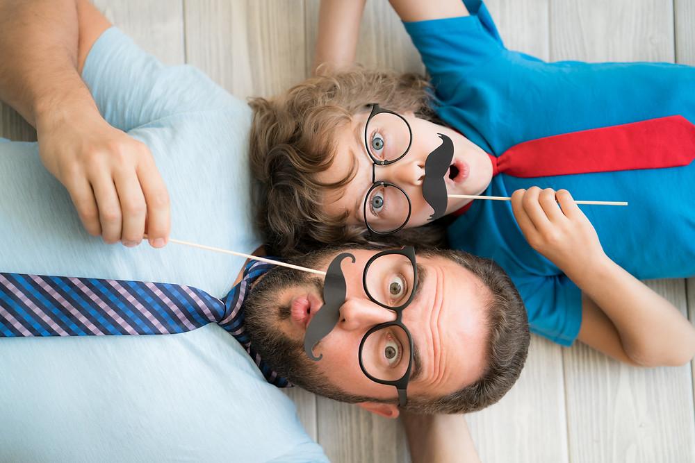Pai e filho com bigode de papel