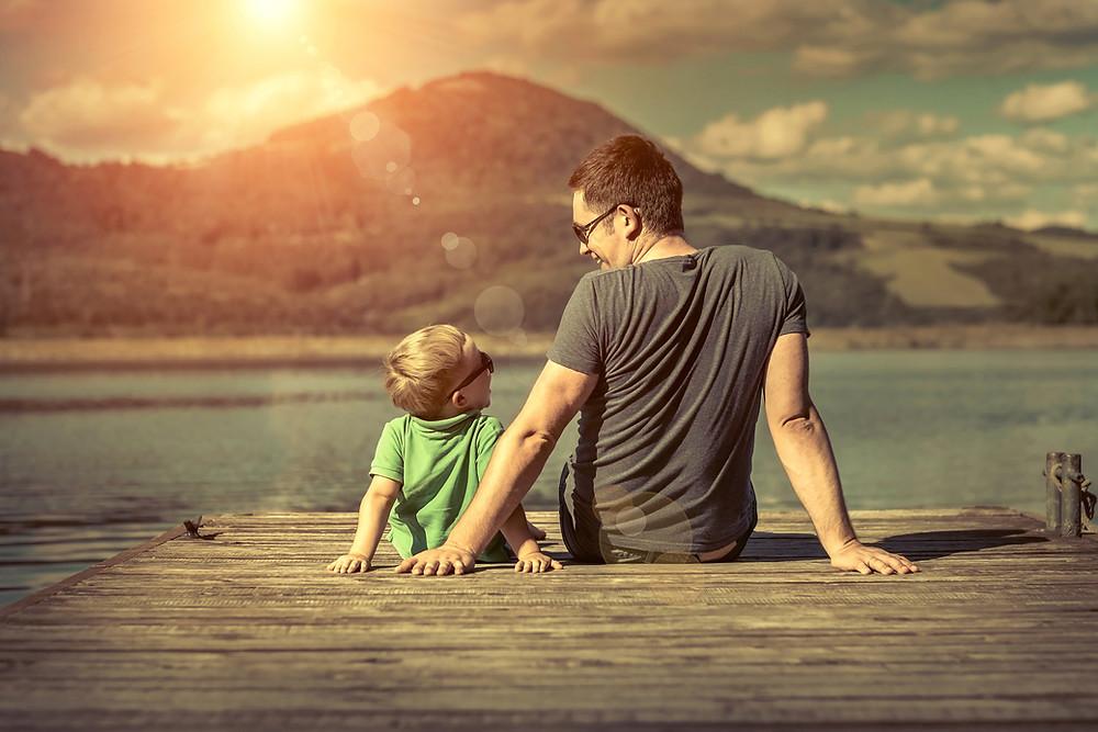 Pai e filho apreciando o pôr do sol