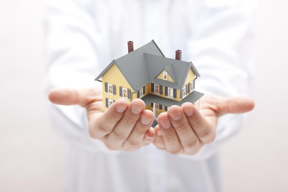 Mãos apresentando a casa