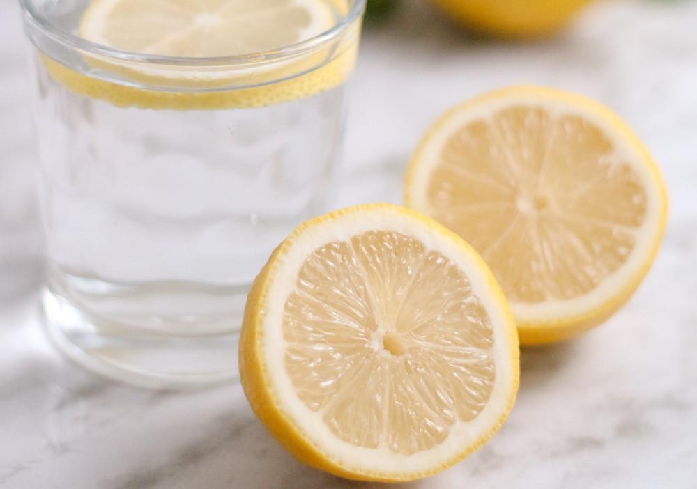 Ein Glas Wasser mit zwei Zitronenhälften.