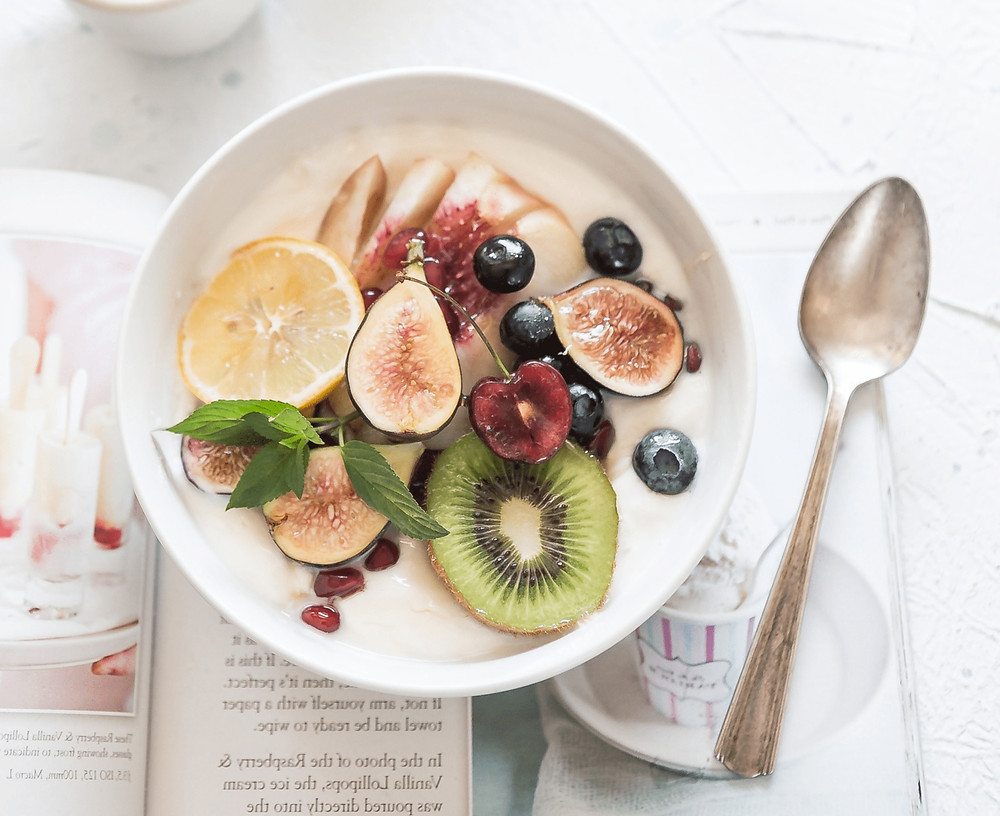Foto einer Schale Müsli mit Früchten, ein Löffel und eine Zeitschrift.