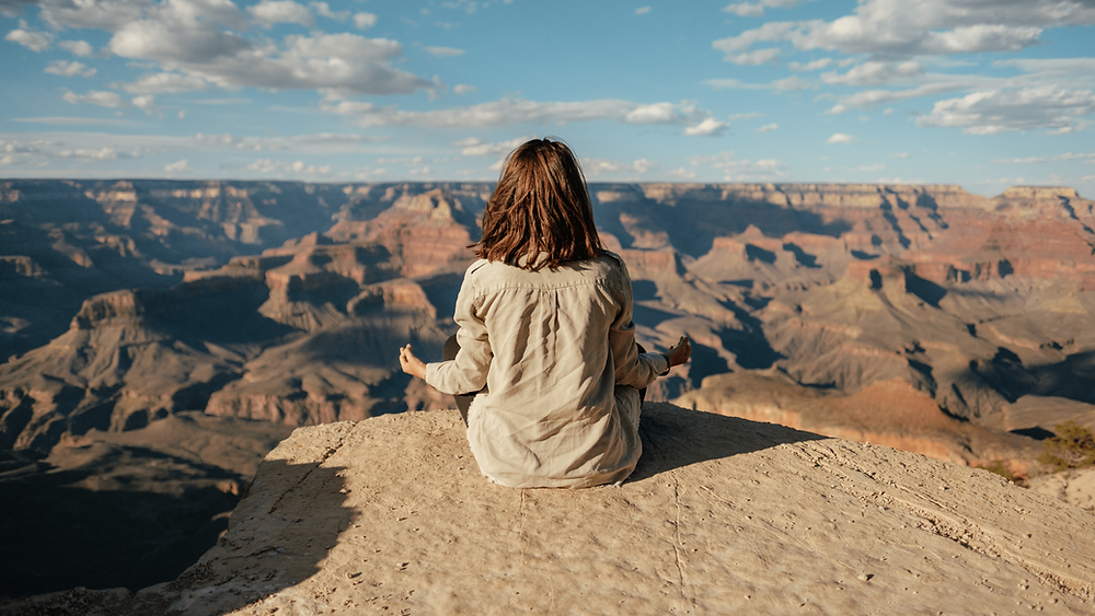 Frau einer meditierenden Frau auf einem hohen Berg.