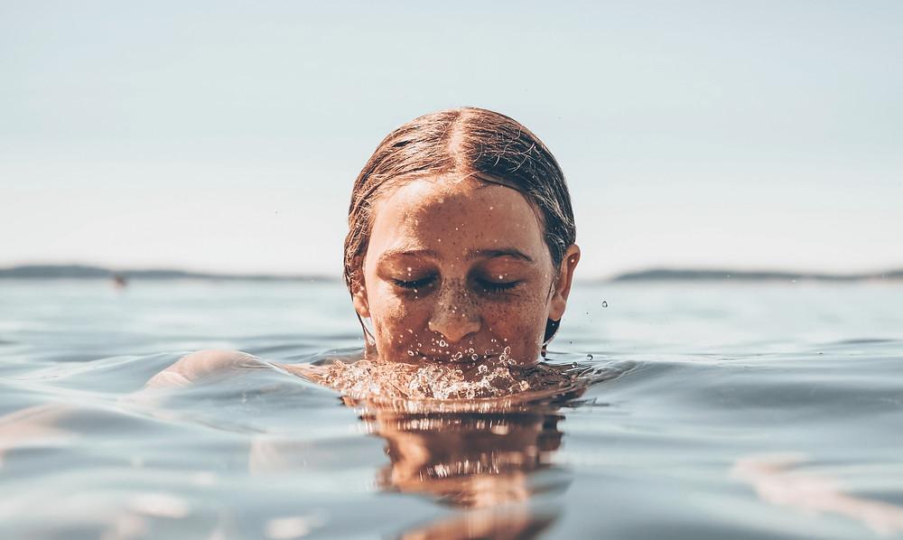 Mädchen taucht ins Wasser ein.