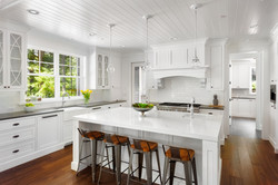 White Kitchen Interior with Island, Sink, Cabinets, and Hardwood Floors in New Luxury Home with Ligh