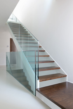 wooden stairs with glass balustrade in modern interior and white epoxy flooring