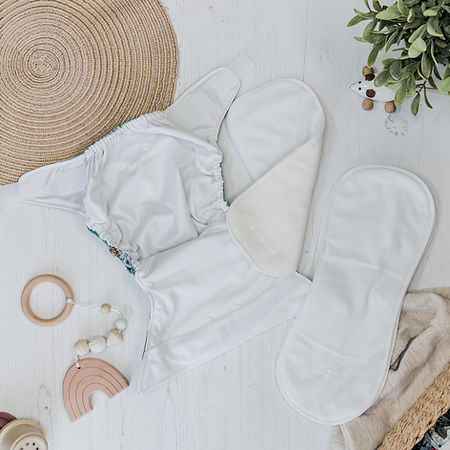 all in two nappy flatlay with boosters at the side