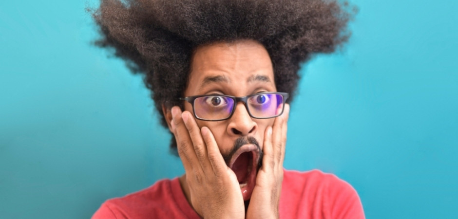 Black man with glasses and afro here looks shocked and holds hands to face.