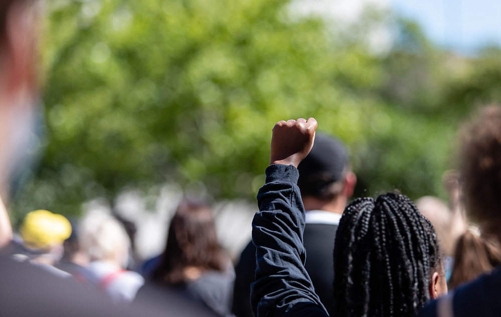 An attendee at a rally against police brutality raises her fist in solidarity and resistance June 13 at Rosa Parks Circle in Grand Rapids.