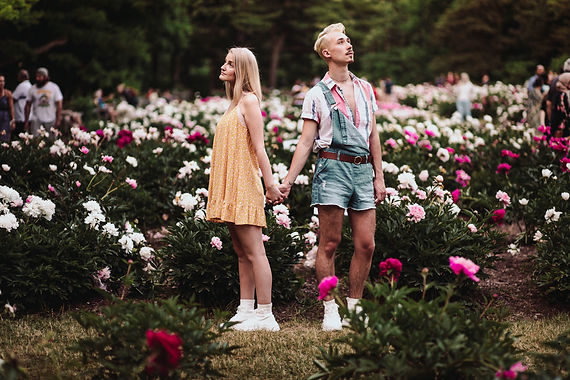 A couple holds hands with their backs to each other, looking off into the distance, in a field of peonies. The partner on the left is a blonde woman wearing a yellow dress and the partner on the right is wearing a striped shirt and jean short overalls.