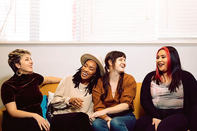 Four doulas sit together, laughing on a couch. Left to right; doula has short blonde hair and brown shirt; doula has shoulder-length locs and a tan shirt; doula has long brown pigtails and an orange shirt; doula has long dark brown hair with bright red money pieces and a white shirt.