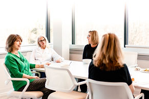 Four female medical practitioners sit around a break table. The picture is clean with a white background. One doctor is in focus, listening to her colleages.