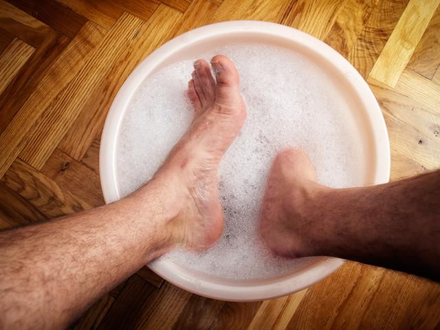 Man soaking his feet in a washbowl..jpg