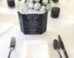 Floral and silver bauble table centrepieces, black cutlery and menus for corporate event