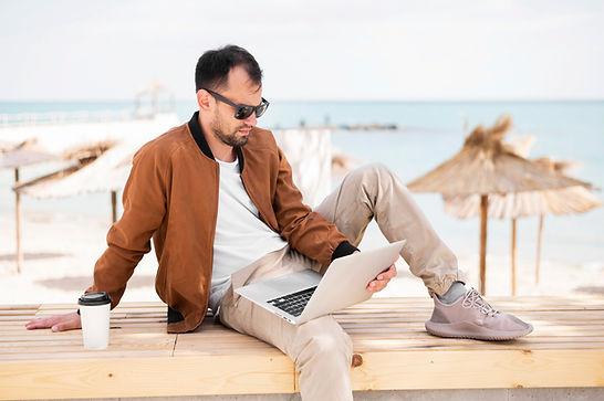side-view-man-working-laptop-beach.jpg