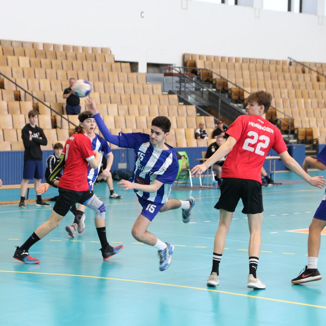 שחקן נוער אסא תל אביב מנתר בין שחקני הגנה תוך כדי זריקת כדור לשער