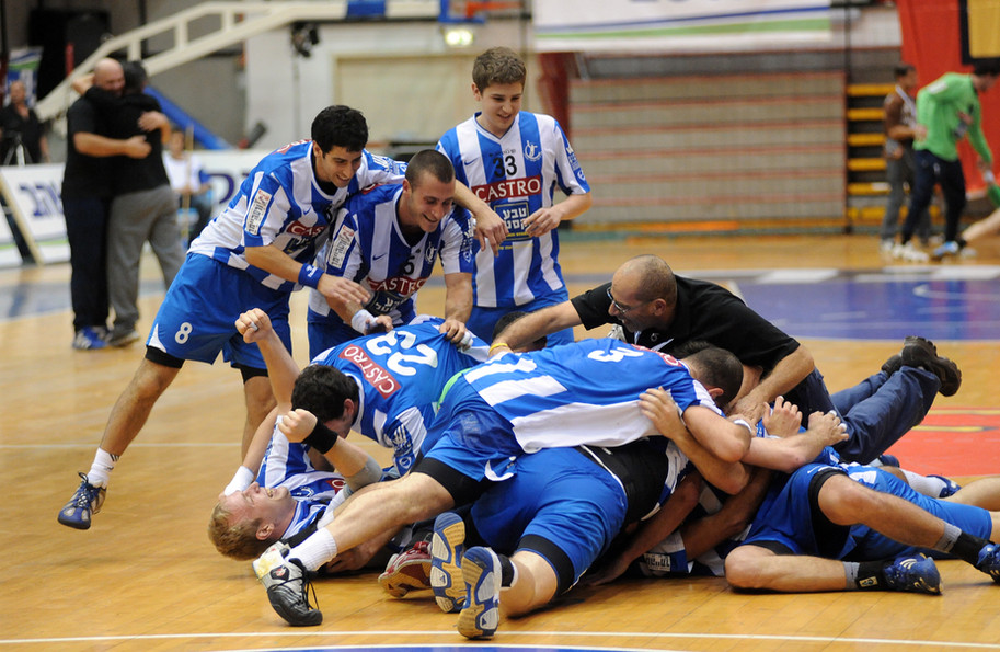שחקני הקבוצה הבוגרת קופצים אחד על השני בערימה על המגרש